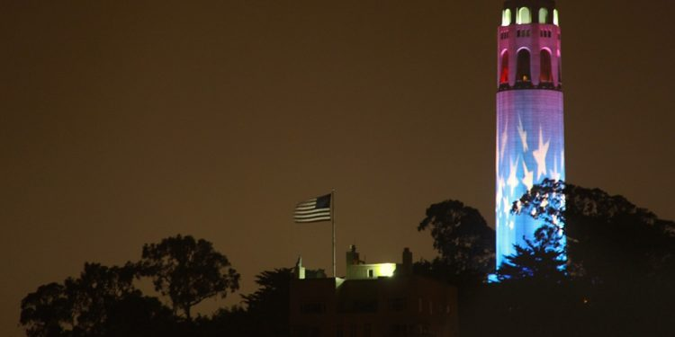 American flag blowing atop a hill with stars projected on a tower.