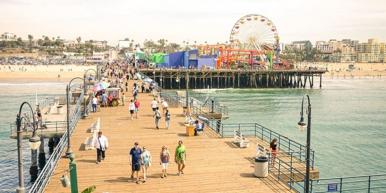Wooden pier extending over the water with metal streetlights and wooden benches. People milling about. Beach off to the left and Ferris wheel off to the right.