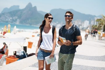 Woman and man walk along a pavement sidewalk beside the beach. She is holding a map and he is holding a book.