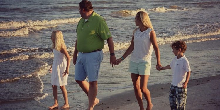 Little girl, dad, mom, and little boy holding hands and walking on the beach.