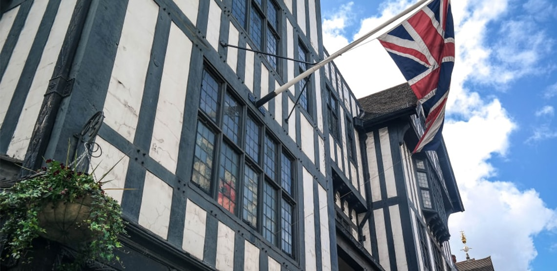 The Union Jack flag hanging off front of a shop, white with black stripes horizontal and vertical.