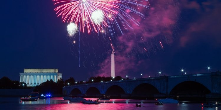 Fireworks over the water with boats floating down below. Lincoln Memorial and Washington Monument are in the background.