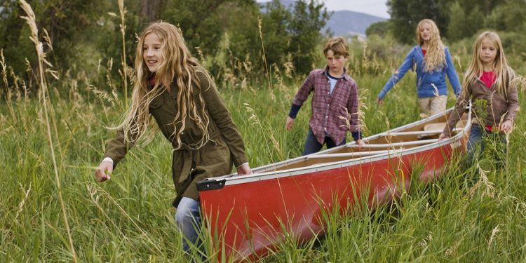 Three blonde haired girls and one blond haired boy carrying a red canoe through long green grass.