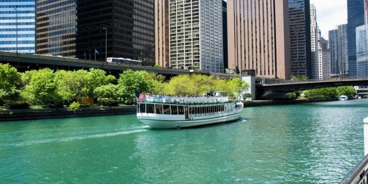 A tour boat motors down the Chicago River with sky rises in the background.