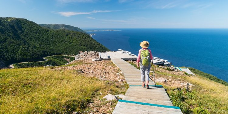 Woman with walking stick walks on boardwalk trail along crest of a hill beside the ocean. The trail continues down the hill and along the coast.