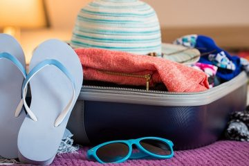 Open suitcase on a bed with sweater, swimsuits, sunhat, flip flops, and sun glasses.