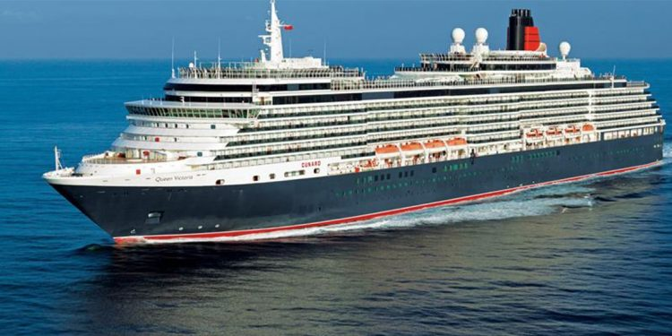 Cruise ship with blue and red hull on the ocean.