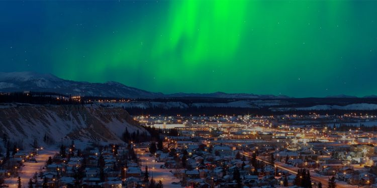 The green northern lights play over glowing lights in a city in a valley.