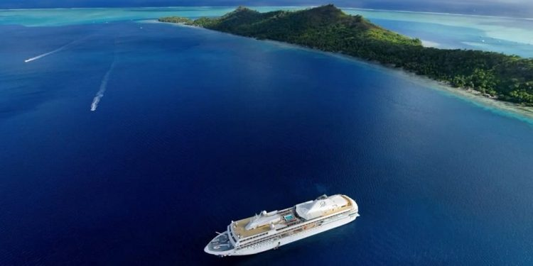 Overhead view of a cruise ship just offshore an island.