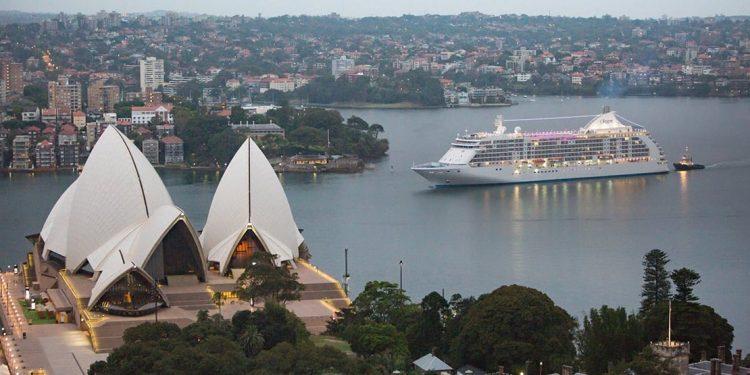 White cruise ship sails into harbor.