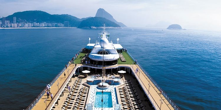 Top deck of a cruise ship with swimming pool and people looking over the railing.
