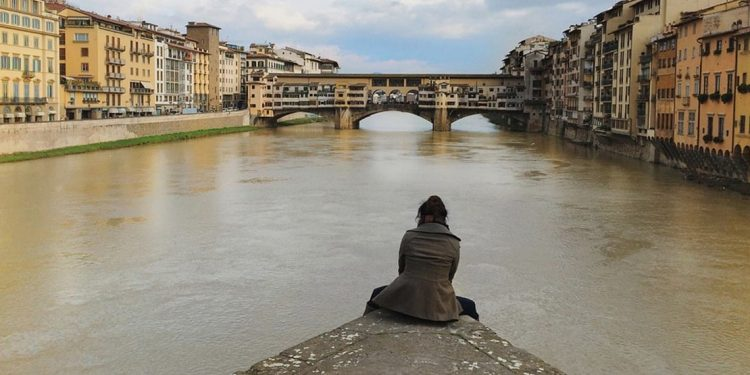 A woman sits on the edge of a piece of concrete in the middle of a river. There are joined buildings on either side and a bridge up ahead.