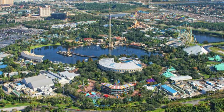Overhead view of the park, including a large lake, dome-like structure, and roller coasters.