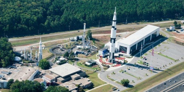 Overhead view of the US Space and Rocket Center: rectangular building, rocket, large parking lot, and various towers.