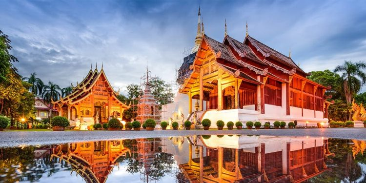 A beautiful golden colored temple with round bushes lining the walkway up to it and a pool of water off to the side.