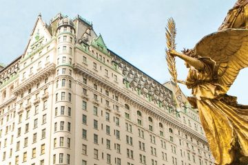 Corner of the hotel with beige walls and green trim with gold angel statue in the foreground.