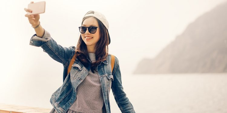 A teenage girl takes a selfie in front of the water and mountain.