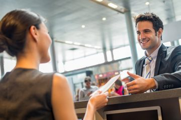Smiling airline employee hands someone their passport over a counter