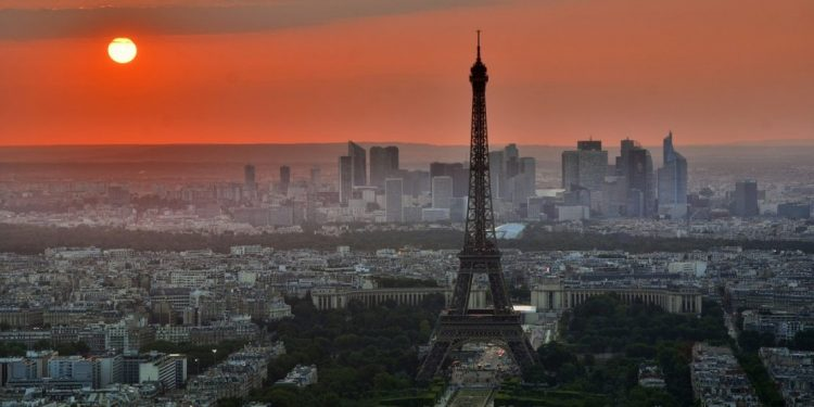 Orange sunset over Paris with Eiffel Tower in the foreground.