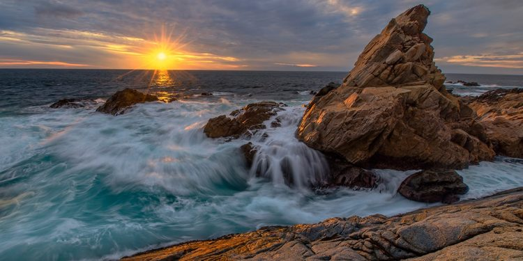 Waves rushing over the rocky shore with the sun setting on the horizon.