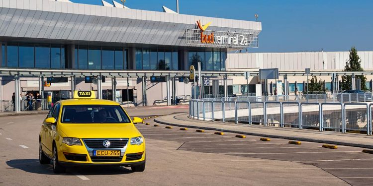 A yellow taxi drives away from the terminal.