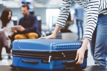 Woman reaches down to grab a blue suitcase off the conveyor belt at the luggage claim.