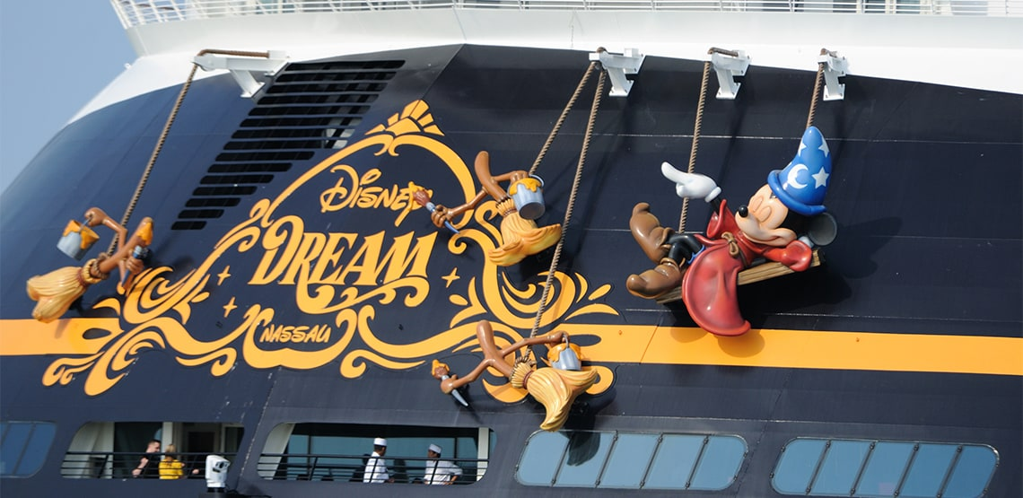 The back of a Disney cruise ship with Mickey and the brooms from Fantasia hanging off the back.