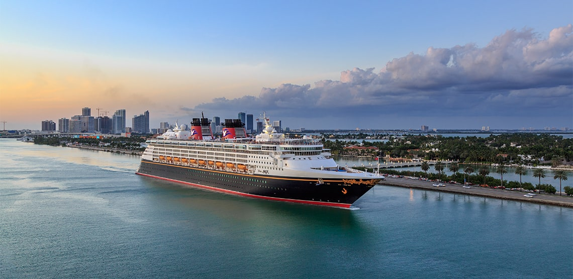 A view of a Disney cruise ship sailing beside the shore.