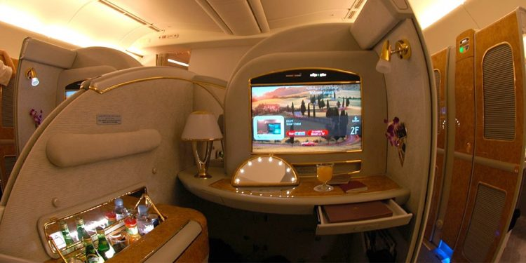 Suite on board an airplane with a beverage fridge and large screen TV.
