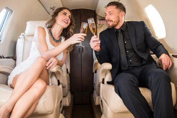 A man and woman in fancy dress sitting in comfortable chairs on board and toasting with champagne.