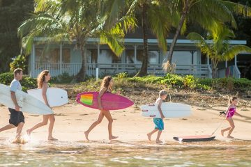 Two parents and three children carry surfboards along the beach at the water's edge with a cottage in the background.