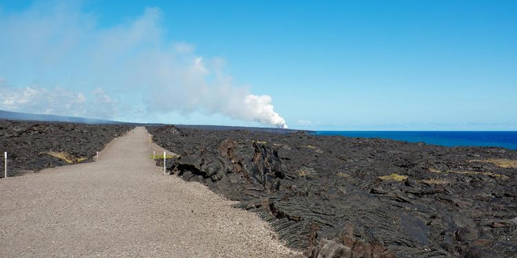Trail through black and bumpy formations of dried lava.