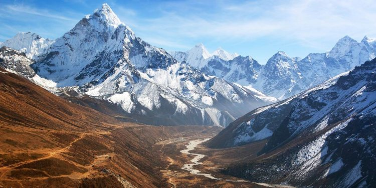 A view of the Himalayas, a river flowing through the valley between craggy mountain peaks covered in snow.