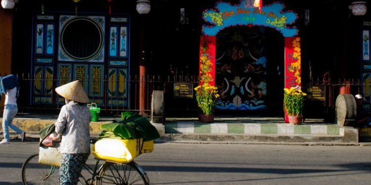 Woman walking beside her bike outside of a colorful building in Hoi An.