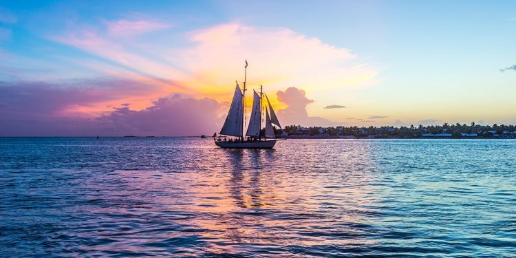 A sailboat out on the ocean, the purple sunset staining the water with its lavender hues.