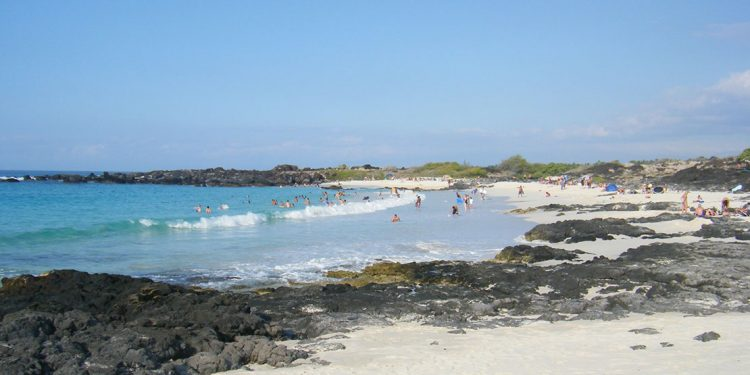 Gentle waves rolling onto shore as people play in the water and sunbathe on the sand.