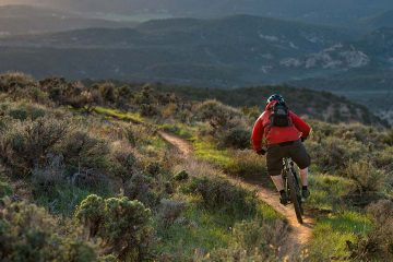 A man wearing a red jacket mountain bikes down a single track trail in a hilly landscape.
