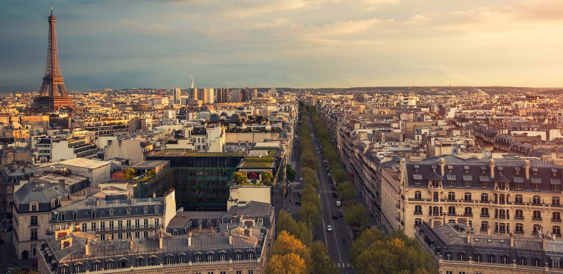 A view of Paris from above, looking down a street lined with trees with the Eiffel tower in the background.