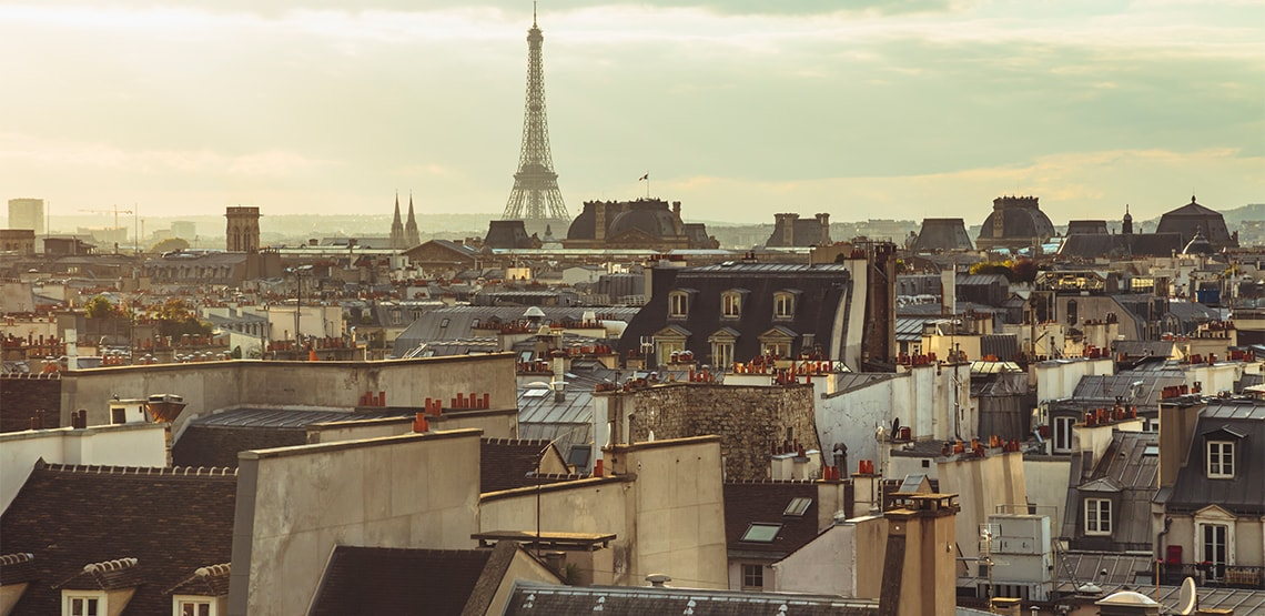 A view of the tops of buildings with the Eiffel Tower in the distance.