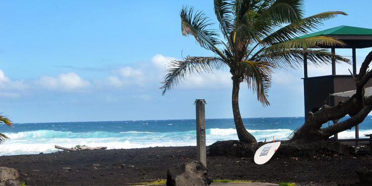 Black sand next to a crashing surf. A surfboard sits near a lifeguard hut.