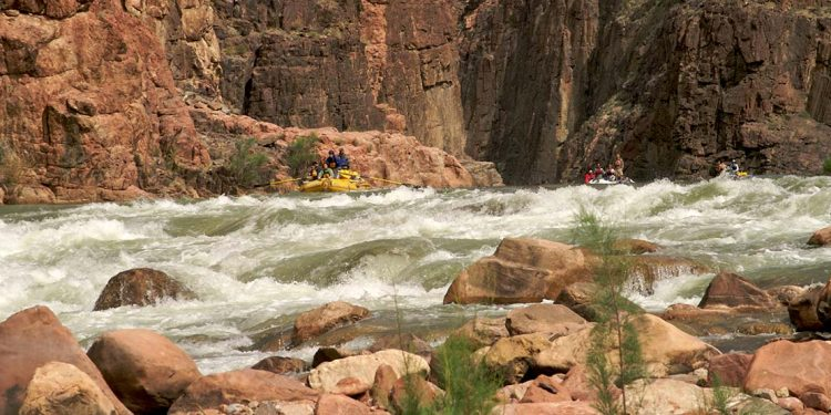 Three rafts approach a set of rapids with rock wall behind them.