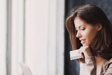 A woman holds a credit card as she looks intently at the screen of her laptop.