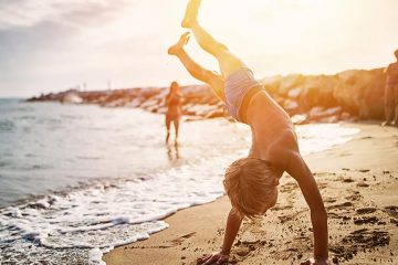 Child doing a handstand on the beach