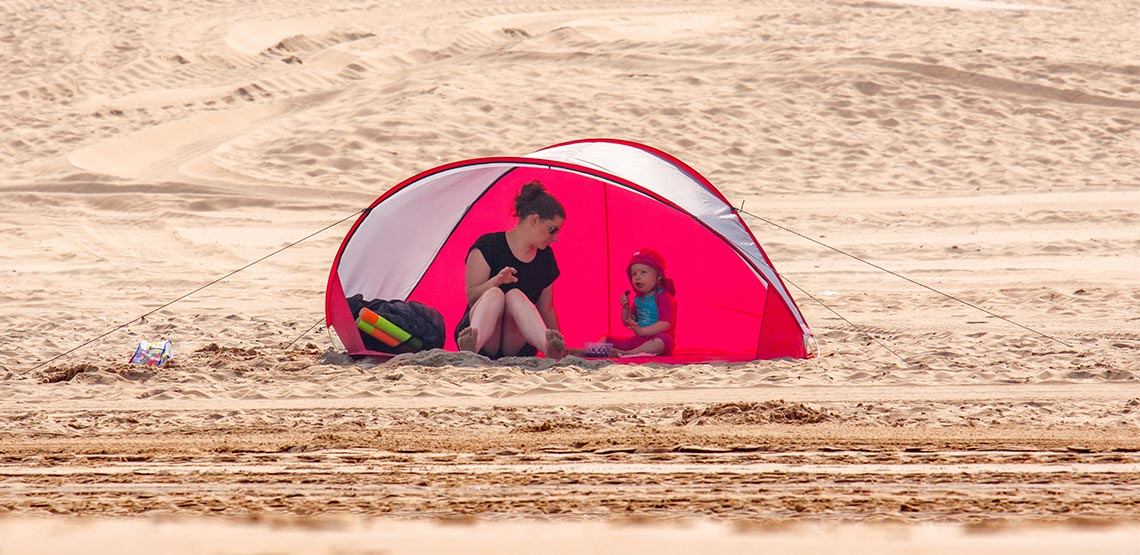 Woman and child sitting under sunshade tent on the beach.