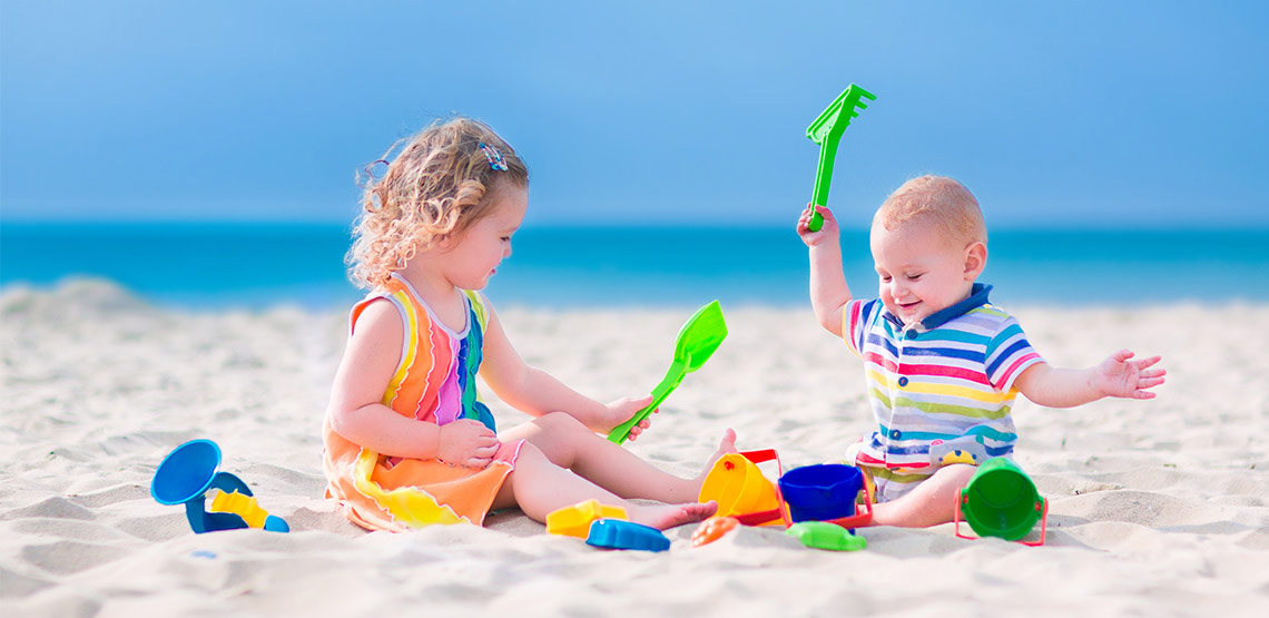 Two young children sitting and playing on the beach.