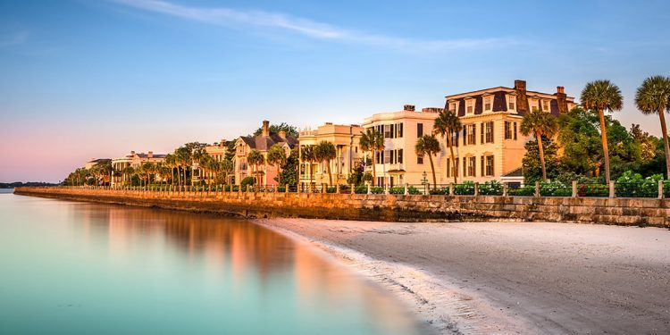 Old southern houses along a waterfront lined with palm trees.