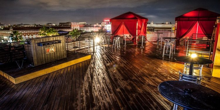An outdoor dance floor on the top of a building at night with red VIP tents and a DJ station.