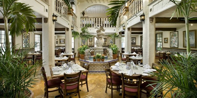 A white dining room at a restaurant with a fountain in the middle.