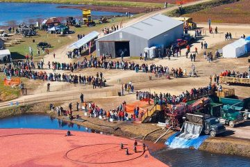 Lake with cranberries floating in water. Big silver shed with various people milling around. Tractors and trucks.