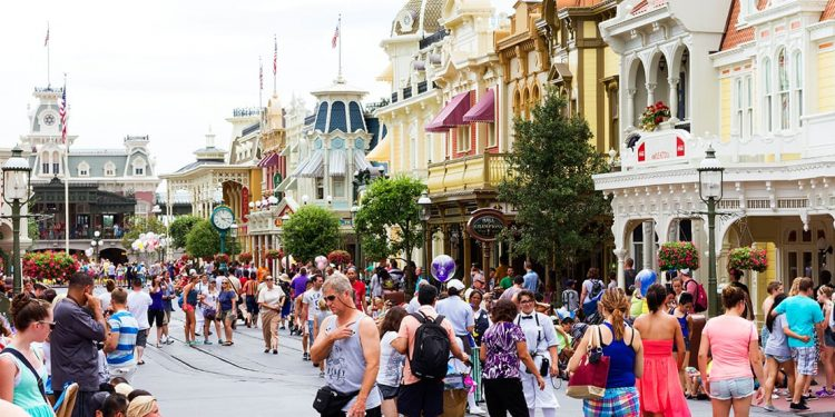 A crowded street at Disney World lined with streetlamps and colorful storefronts.
